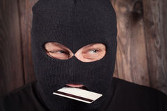Hacker holding a credit card Royalty Free Stock Photo