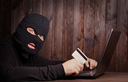 Hacker holding a credit card Stock Image