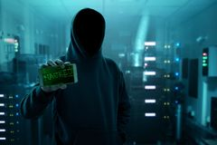 Hacker holding mobile phone in server room royalty free stock photo