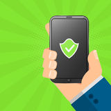 The hacker is holding a secure gadget in his hands. Electronic high-tech phone smartphone. The system is protected. Green shield o Royalty Free Stock Photos