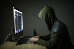 A hacker in a hood on a dark background hacking computer networks in dark room royalty free stock photo