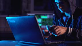 Hacker in the hood holding the phone in his hands trying to hack the mobile device cloud in neon light. Cyber security. Hacker in the hood holding the phone in stock video footage