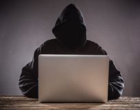 A hacker with a hood with laptop Stock Photography