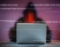 A hacker with a hood with laptop Royalty Free Stock Images