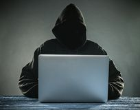 A hacker with a hood with laptop Stock Images