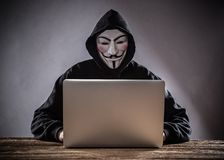 A hacker with a hood with laptop Stock Photo