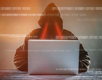A hacker with a hood with laptop Stock Photos