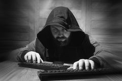 The hacker in the hood sits and works behind the computer Royalty Free Stock Images
