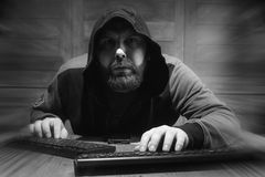 The hacker in the hood sits and works behind the computer. A bearded man in a hood sits and works behind a computer hacker Stock Images