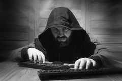 The hacker in the hood sits and works behind the computer. A bearded man in a hood sits and works behind a computer hacker Stock Image