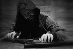 The hacker in the hood sits and works behind the computer. A bearded man in a hood sits and works behind a computer hacker Royalty Free Stock Image