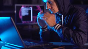 Hacker in a hood thinking about the problem of hacking or malware infection on the background of screens with codes. In neon light. The concept of cybersecurity stock video footage
