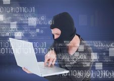 Hacker with hood using a laptop in front of blue background. Digital composite of Hacker with hood using a laptop in front of blue background Royalty Free Stock Photos