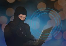 Hacker with hood using a laptop in front of digital background. Digital composite of Hacker with hood using a laptop in front of digital background Royalty Free Stock Photos