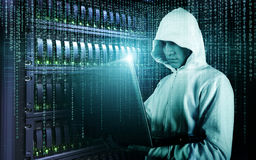 Hacker in Hoodie Standing in the Middle of Data Center full of Rack Servers and Hacking it with His Laptop. royalty free stock image
