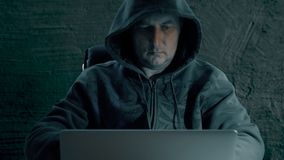 Hacker in a hoody sweatshirt is sitting at table at night and coding. Hacker man in internet. Hacker write and glue. Sticker to laptop. Techology criminal stock footage