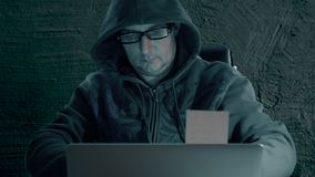 Hacker in a hoody sweatshirt and wearing glasses is sitting at table at night and coding. Hacker man removes memo from. Laptop screen. Front view stock video