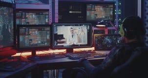 Hacker intercepting doctors video call. Medium close-up of a hacker intercepting a video call between two doctors stock video