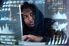 Hacker with a laptop, infographics. Worried African American hacker wearing a hoodie and looking with an alert while typing at his laptop. Graphs and Stock Images