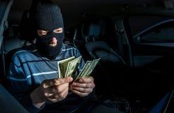 Hacker with a laptop inside a car Stock Photos