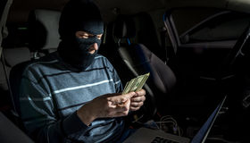 Hacker with a laptop inside a car Royalty Free Stock Photo
