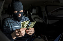Hacker with a laptop inside a car Stock Image