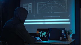 Hacker with laptop. Man in the hood from his back sitting and working at laptop as hacker, with world map on wall in background. Then he take off usb flash disk stock footage