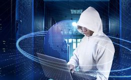 Hacker with laptop among servers in your data center on background of the hologram cyber attack and the planet earth. stock images