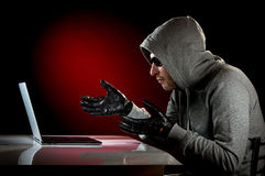 Hacker with laptop Royalty Free Stock Image