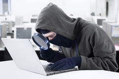 Hacker looking for information at office Stock Photo