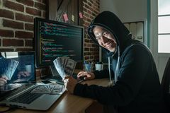 Hacker looking round and holding banknote. Hacker looking round and holding banknote smiling with pure evilness at his working place royalty free stock photography