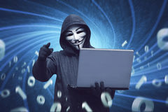 Hacker man with anonymous mask holding laptop Stock Photography
