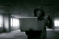 Hacker man with anonymous mask holding laptop while standing. Against dark room stock photo