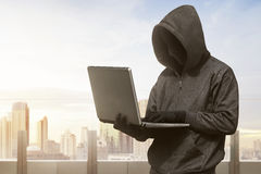 Hacker man with anonymous mask using laptop to hacking. In the modern building royalty free stock image
