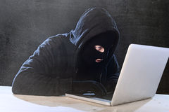 Hacker man in black hood and mask with computer laptop hacking system in digital intruder cyber crime concept Royalty Free Stock Photos