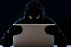 Hacker man in black hood and mask with computer laptop hacking system in digital intruder cyber crime concept. Hacker man in black hood and mask with computer stock image