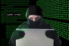 Hacker man in black using computer laptop for criminal activity hacking password and private information. Cracking password too access bank account data in Stock Image