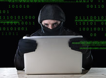 Hacker man in black using computer laptop for criminal activity hacking password and private information Stock Image