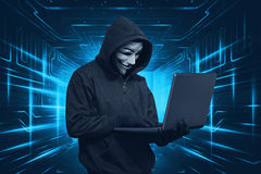Hacker man with mask using laptop while standing Stock Images