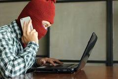 Hacker mascarado com o telefone e o portátil espertos móveis que rouba dados da informação importante Conceito da segurança da re fotografia de stock royalty free