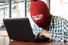 Hacker mascarado que veste um passa-montanhas que rouba dados da importância do portátil Conceito do crime do Internet imagens de stock