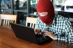 Hacker mascarado que veste um passa-montanhas que rouba dados da informação com portátil Conceito do crime do Internet imagens de stock royalty free