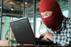 Hacker mascarado que veste um passa-montanhas que rouba dados do portátil Conceito do crime do Internet imagem de stock royalty free