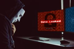Hacker mascarado sob a capa usando o computador para cortar no sistema e para empregar o processo de escape dos dados fotos de stock royalty free