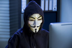 The hacker in a mask of Guy Fawkes. Uses the computer late at night Royalty Free Stock Photos
