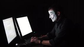 The hacker in the mask hacks the program. the digital extortion gets access to other people`s information. computer stock video footage