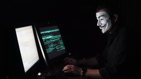 The hacker in the mask hacks the program. the digital extortion gets access to other people`s information. computer stock video