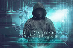 Hacker in mask typing keyboard hacking binary data Royalty Free Stock Image