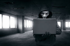 Hacker with mask using laptop Royalty Free Stock Photo