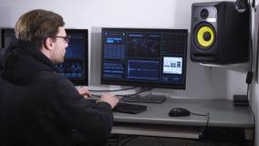 Hacker mit Gläsern auf den Augen in der schwarzen Jacke mit einer Haube, verlassen seinem Auftrag des Brechens der geheimen Daten stock video